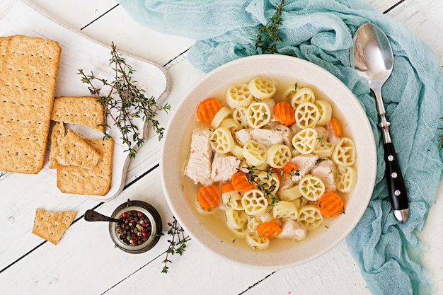 Dietary soup with turkey or chicken fillet with pasta ruote and herbs. flat lay. top view Premium Photo