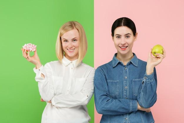 ダイエットの概念。健康に役立つ食品。スタジオで果物と不健康なケーキのどちらかを選ぶ美しい若い女性。 無料写真