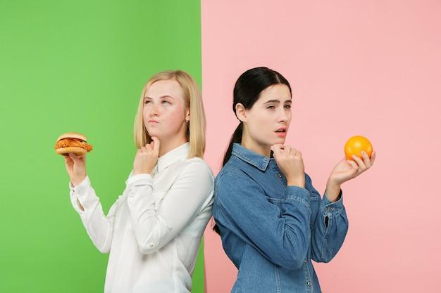 ダイエットの概念。健康に役立つ食品。スタジオで果物と不健康なファーストフードのどちらかを選ぶ美しい若い女性。人間の感情と比較の概念 無料写真
