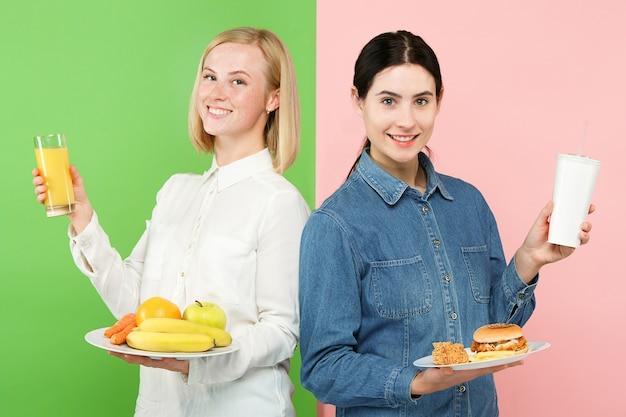 Concetto di dieta. cibo sano e utile. belle giovani donne che scelgono tra frutta e fast food malsano in studio. emozioni umane e concetti di confronto Foto Gratuite