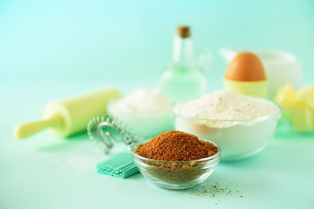 Different baking ingredients - butter, sugar, flour, milk, eggs, oil, spoon, rolling pin, brush, whisk Premium Photo