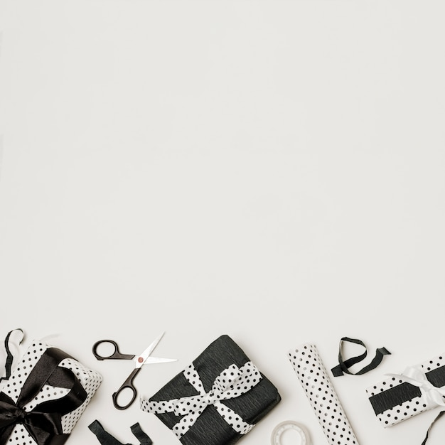 Different black and white wrapped gift boxes with scissor and design paper Free Photo