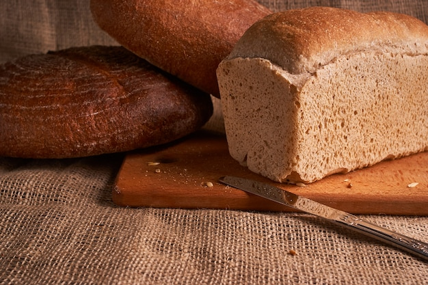 Different bread and wheat on the rustic table. Premium Photo