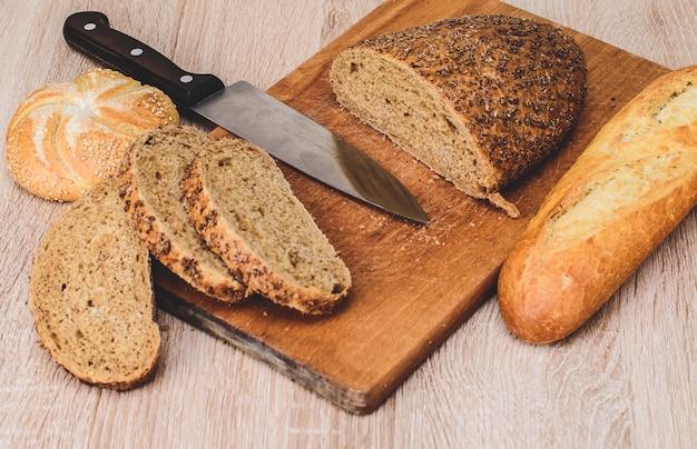 Разные породы на деревянных фоне. нож на деревянной доске с хлебом и разными булочками на столе. хрустящий хлеб на деревянной доске. Premium Фотографии