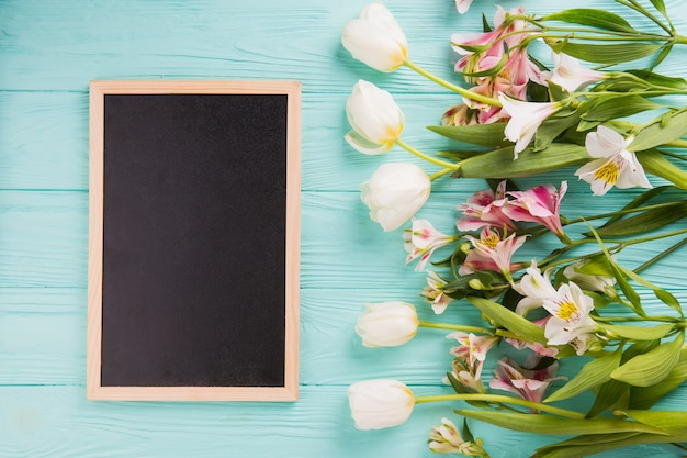Different bright flowers with chalkboard on table Free Photo
