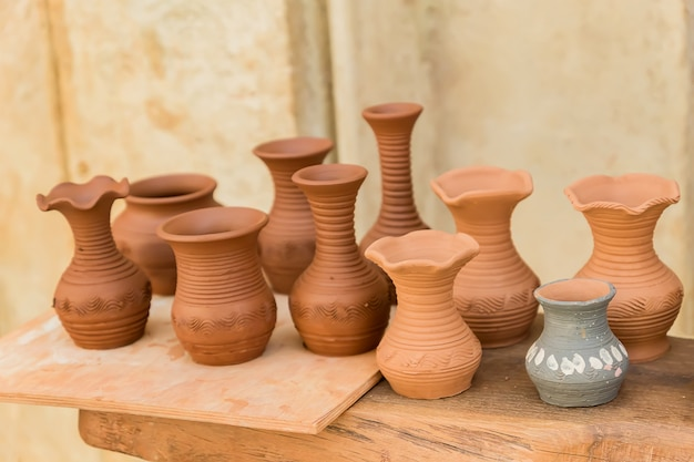 Different clay pots on a wooden table Premium Photo