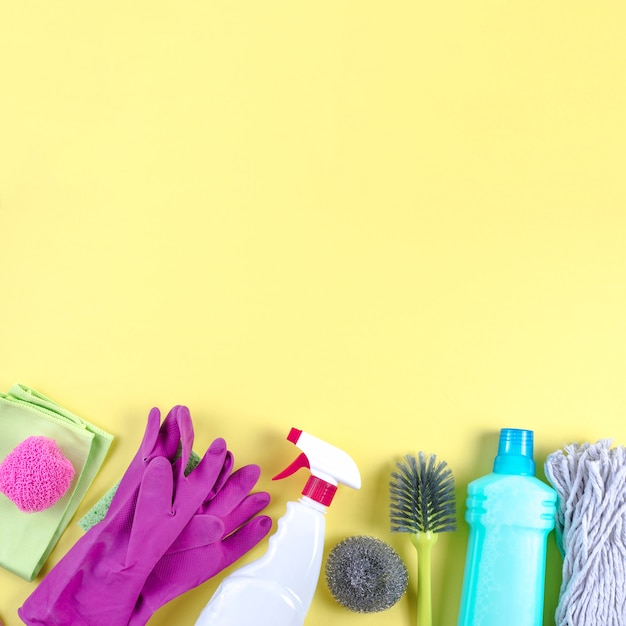 Different cleaning equipments on yellow backdrop Free Photo