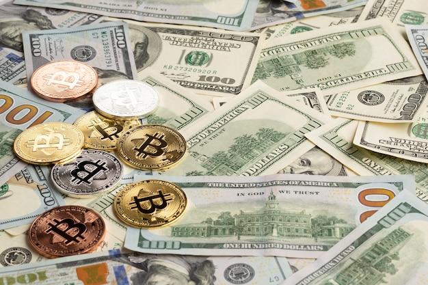 Разноцветный биткойн поверх долларовых купюр Бесплатные Фотографии