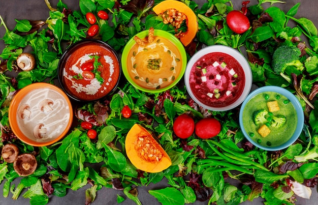 Different colorful vegetable cream soups in a bowls, eating or vegetarian food. Premium Photo