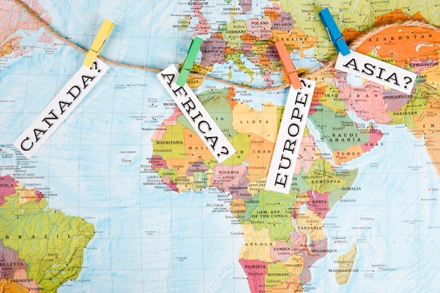 Different continents tag with clothes peg on world map Free Photo