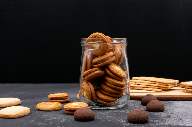 Different cookies in glass jar on dark surface Free Photo