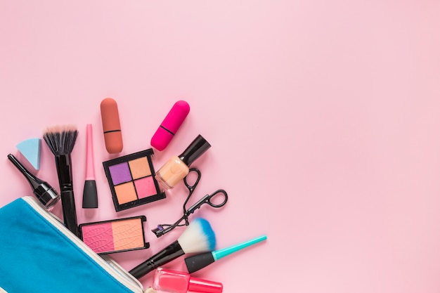 Different cosmetics scattered from blue beauty bag Free Photo
