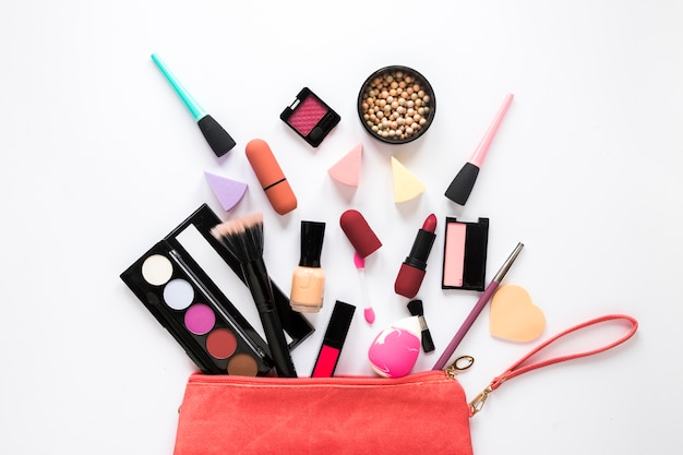 Different cosmetics scattered from red beauty bag Free Photo
