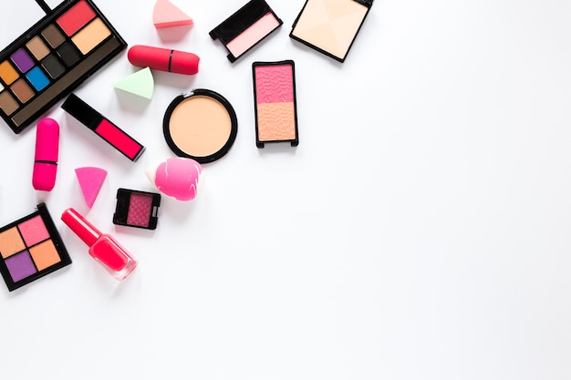 Different cosmetics scattered on white table Free Photo