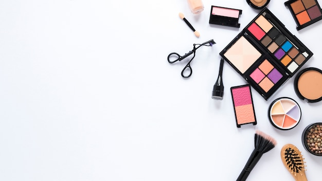Different cosmetics types scattered on light table Free Photo