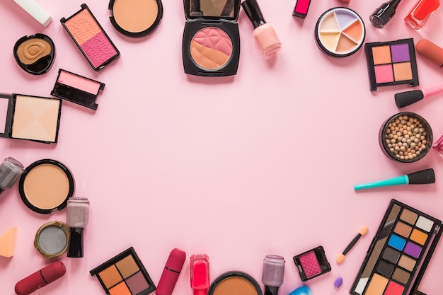 Different cosmetics types scattered on pink table Free Photo