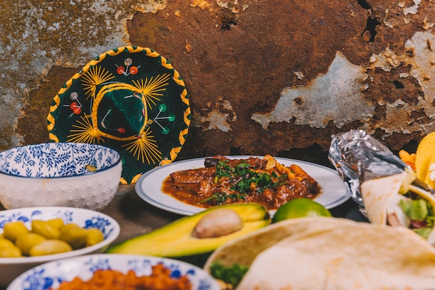 Different delicious mexican dishes over rusty background with mexican hat Free Photo