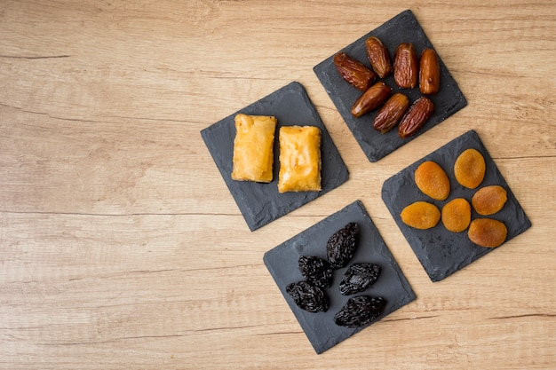Different dried fruits with eastern sweets on table Free Photo