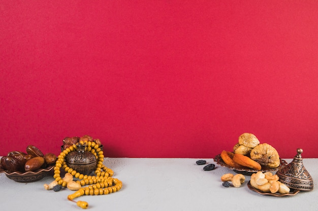 Different dried fruits with nuts and beads Free Photo