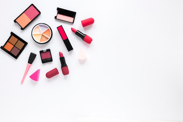 Different eye shadows with lipsticks on table Free Photo