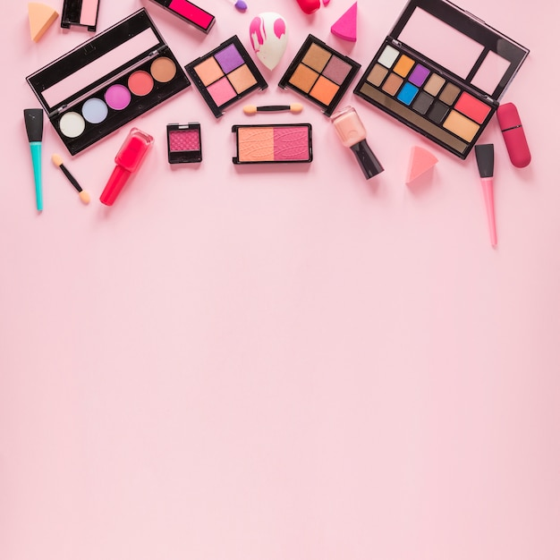 Different eye shadows with nail polish on table Free Photo