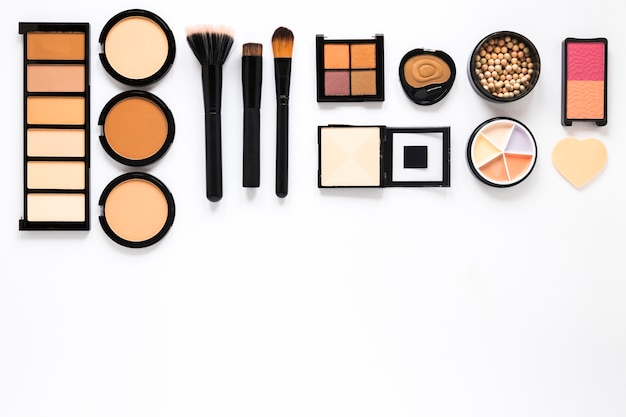Different facial powders with powder brushes on white table Free Photo