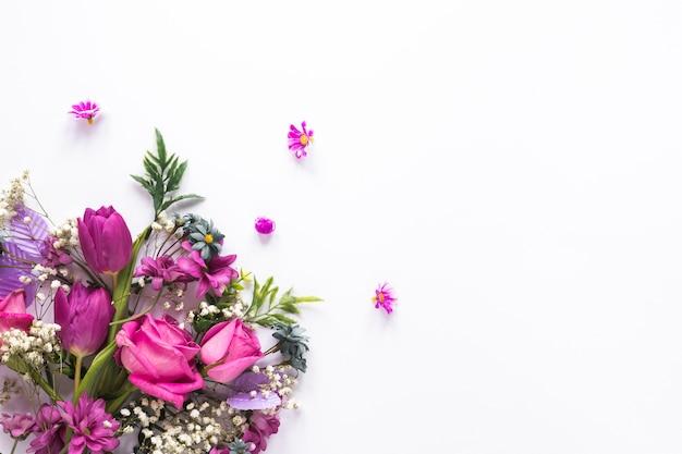 Разные цветы разбросаны на белом столе Premium Фотографии