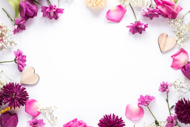 Different flowers with wooden hearts on table Free Photo