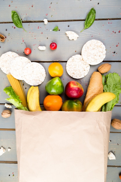 Different food in paper bag on wooden background Premium Photo