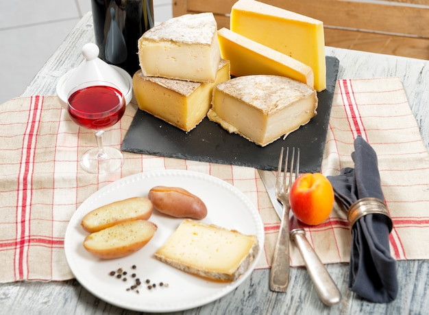 Different french cheeses with a glass of wine Premium Photo