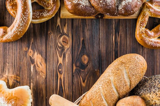 Different freshly baked bread on the wooden background Free Photo