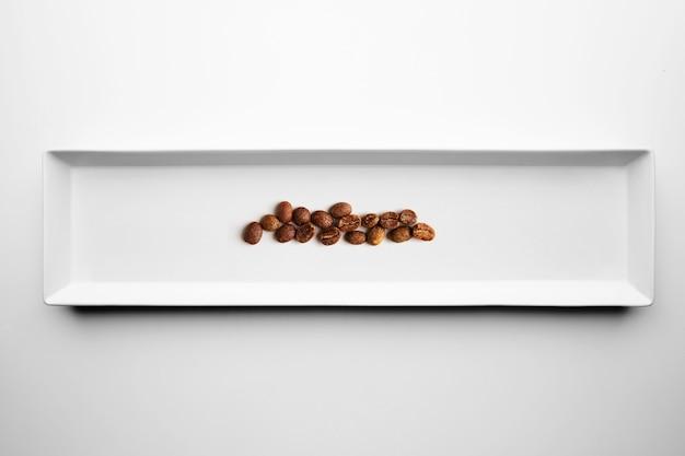 Diversi gradi di torrefazione professionale artigianale caffè isolato su piastra bianca, vista dall'alto Foto Gratuite