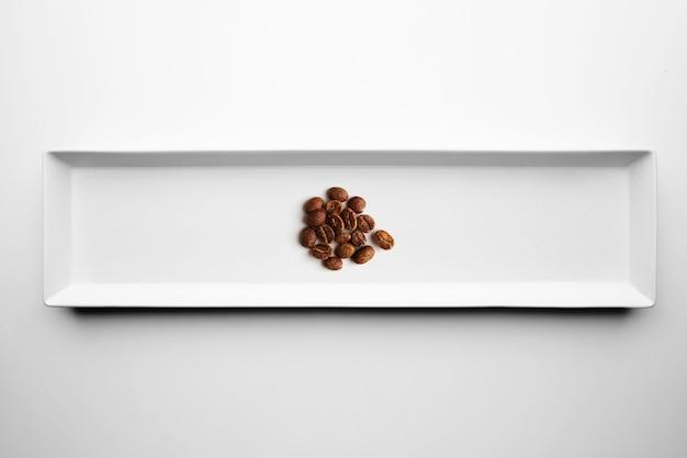 白いプレートに分離された職人のプロの焙煎コーヒーのさまざまなグレード、上面図 無料写真
