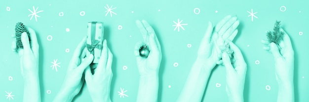 Different hands holding christmas elements green banner background Premium Photo