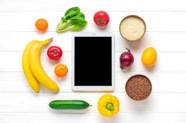 異なる健康食品-ソバ、米、黄色のピーマン、トマト、バナナ、レタス、グリーン、キュウリ、タマネギ、黒い画面のタブレット Premium写真