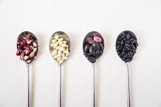 スプーンの中の異なる種類のインゲン豆。白い表面。上面図 Premium写真