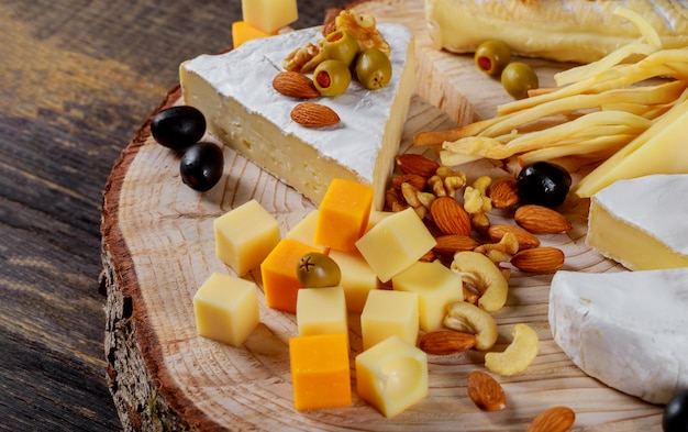 Different kinds of cheese, olives and assorted nuts wood background Premium Photo