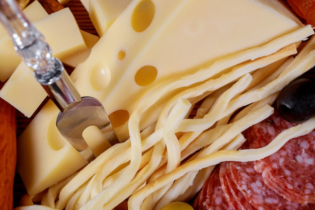 Different kinds of cheese, olives and sausage background Premium Photo