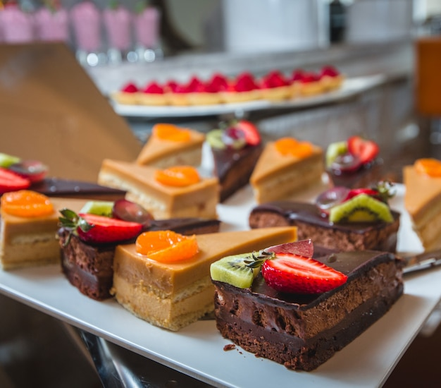 Different kinds of cream, caramel and chocolate cakes with fruits on the top Free Photo