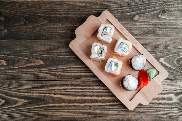 Different kinds of japanese rolls with wasabi and ginger on bamboo tray on wood Premium Photo