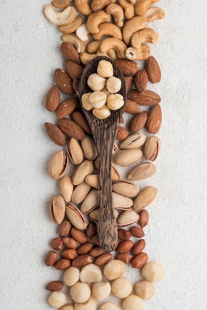 さまざまな種類のナッツとスプーン 無料写真