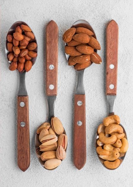 Разные виды орехов в ложках плоской формы Бесплатные Фотографии