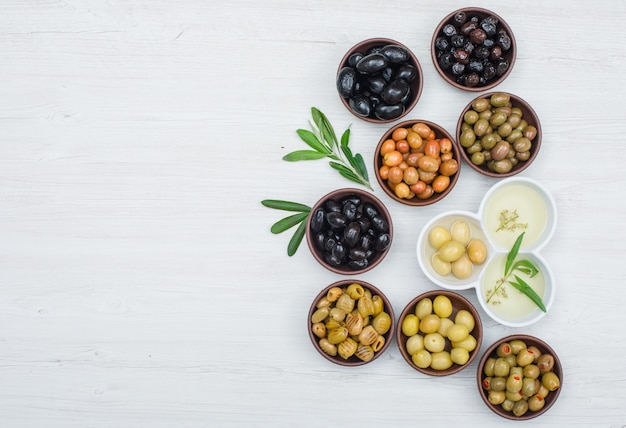 Different kinds of olives and olive oil in a clay and white bowls with olive leaves flat lay on white wood Free Photo