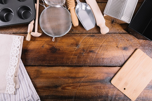 Different kitchen utensil for baking cake on wooden table Free Photo