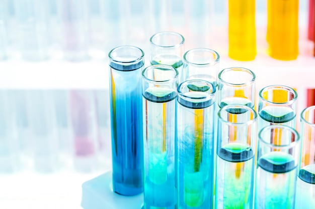 Different laboratory glassware with colored liquids close up Premium Photo
