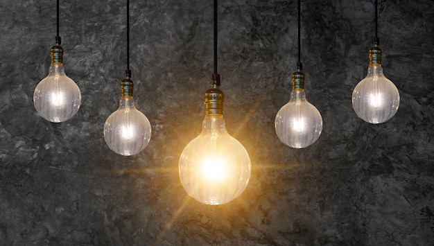 Different light bulb idea many bulbs are arranged in a row and one of them is illuminated. concept idea Premium Photo