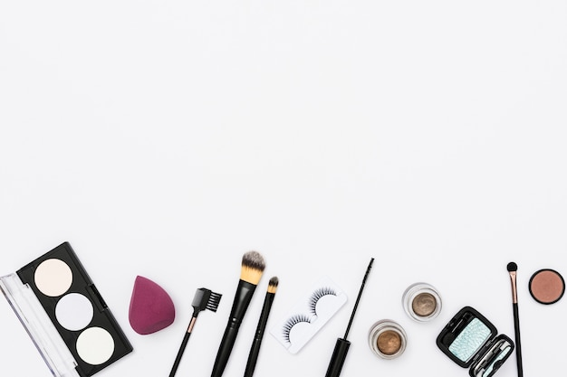 Different makeup cosmetics and makeup brushes on white background Free Photo