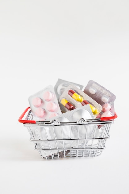 Different medicine blisters in the stainless steel basket on white background Free Photo