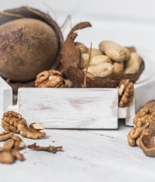 白い木製の背景に別のナッツのクローズアップ 無料写真