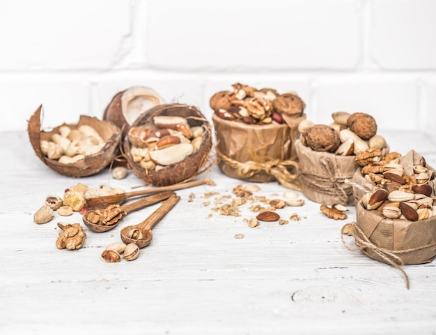 Различные орехи в тарелках и деревянных ложках крупным планом на белом деревянном фоне, концепция здоровой силы белка Бесплатные Фотографии